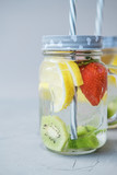Fruit water with lemon and strawberries in a glass jar