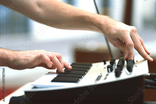 Fotobehang Muziek A synthesizer player during a concert moves knobs and controls the sound
