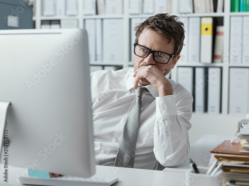 Pensive businessman staring at the computer screen