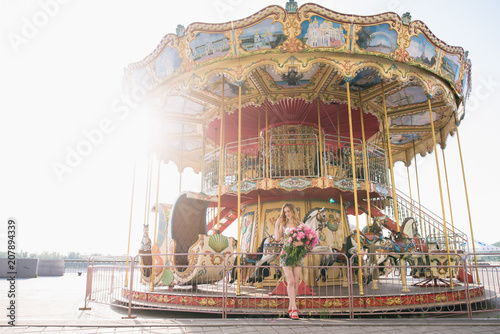 Fotobehang Amusementspark Beautiful girl in a dress with a bouquet of pink peonies in the hands near a vintage carousel