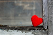 Red lonely heart in a village window