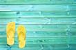 Yellow flip flops on blue planks, summer concept background with copy space