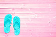 Blue flip flops on pink planks, summer concept background with copy space