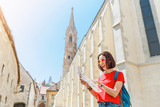 Mixed race woman traveler holding map in hands while looking for some interesting tourist sights and destinations