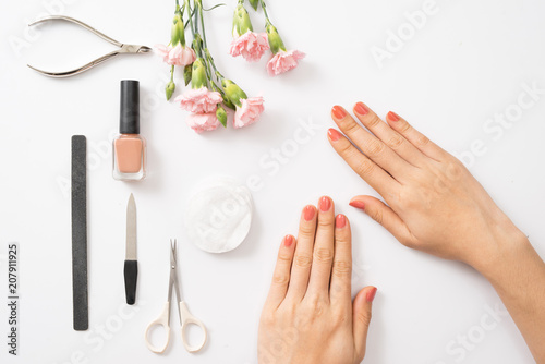 Female hands applying purple nail polish on wooden table with towel and nail set - 207911925