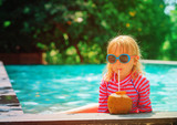 little girl drinking coconut cocktail on beach