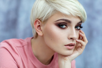 Portrait of young female model in fashionable make up with short hair looking at camera © kiuikson