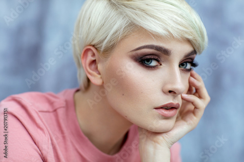 Leinwanddruck Bild Portrait of young female model in fashionable make up with short hair looking at camera