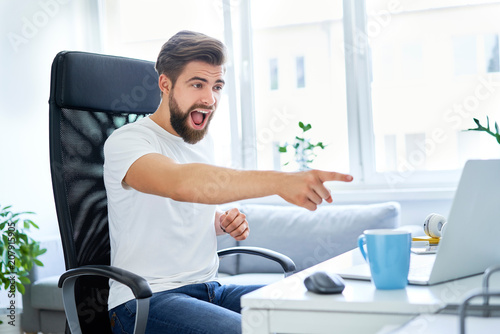 Excited young man, student pointing at his laptop sitting in dorm room