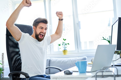 Foto Murales Excited successful man working in office looking on laptop