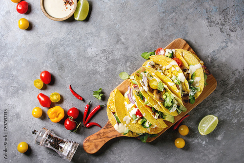 Variety of vegetarian corn tacos with vegetables, green salad, chili pepper served on olive wood board with tomato, cream sauces with ingredients above over grey texture background. Top view, space.