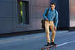 smiling young man riding longboard and using smartphone