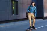 smiling young man riding longboard and using smartphone - 207919100