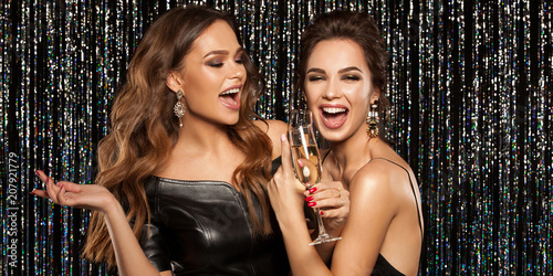 Leinwanddruck Bild Two beautiful young girls smiling and holding a glass of champagne, meeting Christmas and New Year. Clean skin and a hairstyle with bright lips. Photographed on a sparkling background.