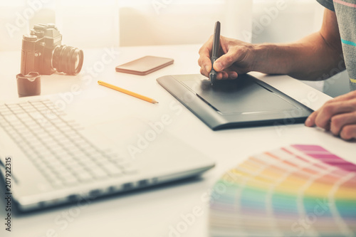 Foto Murales graphic designer at work in office working with digital drawing tablet