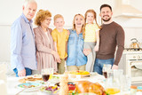 Portrait of carefree two generation family of six posing  at home and smiling   standing at festive dinner table - 207923526