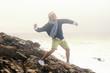 Young man throws stones into the ocean