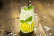 Leinwanddruck Bild - Cold Fresh Lemonade Mojito Cocktail with Ice, Lemon and Mint Leaves in Mason Jar on Rustic Dark Wooden Background. Summer Concept.
