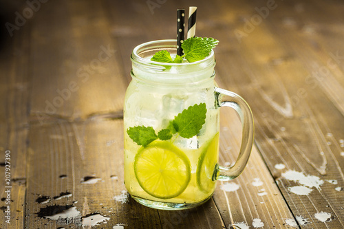 Leinwanddruck Bild Cold Fresh Lemonade Mojito Cocktail with Ice, Lemon and Mint Leaves in Mason Jar on Rustic Dark Wooden Background. Summer Concept.