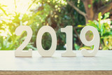 New year concept : wooden nunber 2019 for new year on wood table with sunlight. - 207927514