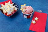 Homemade Star Shaped Sugar Cookies and Homemade Strawberry Ice Cream Served in Red, White, and Blue Paper Products against a Blue Background  - 207928789