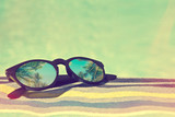 Sunglasses with palm trees reflections on a bath towel, vintage summer concept - 207929576