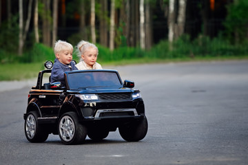 Boy and girl on toy electric car