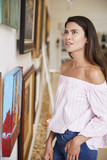 Woman Looking At Paintings In Art Gallery - 207934539