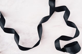 Black ribbon on white marble background layout from above. Copy space for text - 207934575