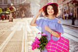 Outdoor portrait of young beautiful happy smiling woman wearing stylish striped dress, hat, holding bright pink straw bag with peonies, posing in street of european city. Summer fashion. Copy space - 207935314