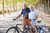Portrait Of Smiling Senior Couple Cycling On Country Road - 207935354
