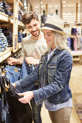 Leinwanddruck Bild Junges Paar beim Shopping nach Jeans Kleidung