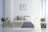 Round rug in front of grey bed with blanket in minimal bedroom interior with poster. Real photo - 207936575
