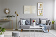 Real photo of a great sofa with cushions and blanket standing in elegant living room interior behind a white table and next to a gold lamp and grey wall with posters