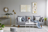 Real photo of a great sofa with cushions and blanket standing in elegant living room interior behind a white table and next to a gold lamp and grey wall with posters - 207936756