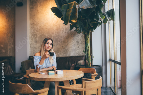 Young hispanic woman at cafe drinking coffee