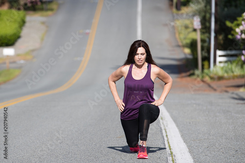 Foto Murales Healthy woman doing a lunge outside