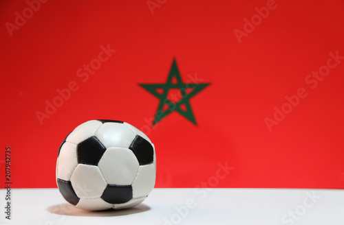 Fotobehang Marokko Small football on the white floor and Moroccan nation flag background. The concept of sport.
