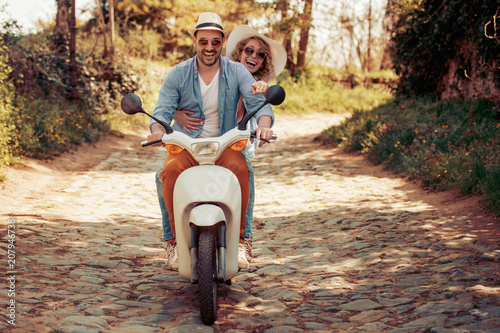 Happy young couple riding a scooter in the city
