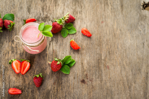 Fotobehang Milkshake Strawberry smoothies in glass on wooden background. Top view. Copy space