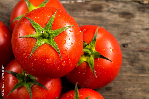 Fresh red tomatoes with waterdrops on wooden background