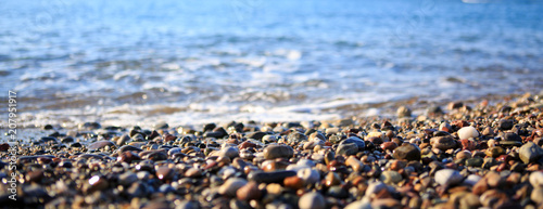 Waves washing over gravel beach, macro shot. - 207951917