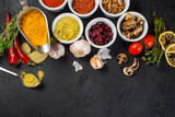 Different spices with raw and dry vegetables on black background. Top view. copy space