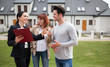 Leinwandbild Motiv Young couple with real estate agent visiting house for sale in residential area