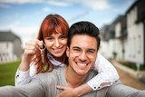 Smiling couple with keys to their new home hugging and looking at camera taking selfie - 207956396