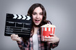 Young beautiful woman holding bucket with popcorn and clapper board on grey background