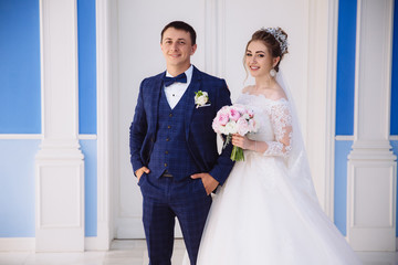 The newlyweds are going to enter the ceremony hall, smiling, the Man in a strict stylish suit and the girl in a white fluffy dress with a bouquet.