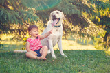 Portrait of cute adorable little Caucasian European baby girl sitting with dog in park outside. Child playing sitting by animal domestic pet. Happy childhood concept - 207964720