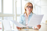 Adult woman in glasses sitting with gadgets at table and reading papers with concentration while working - 207964765