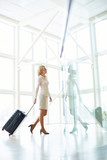 Side view of elegant woman standing with suitcase reflecting in glass wall inside of light hall. - 207965356